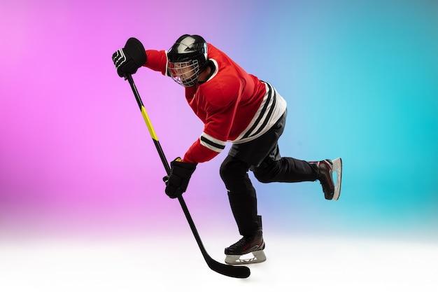 Männlicher hockeyspieler mit dem stock auf dem eisplatz und neonfarbener farbverlaufswand