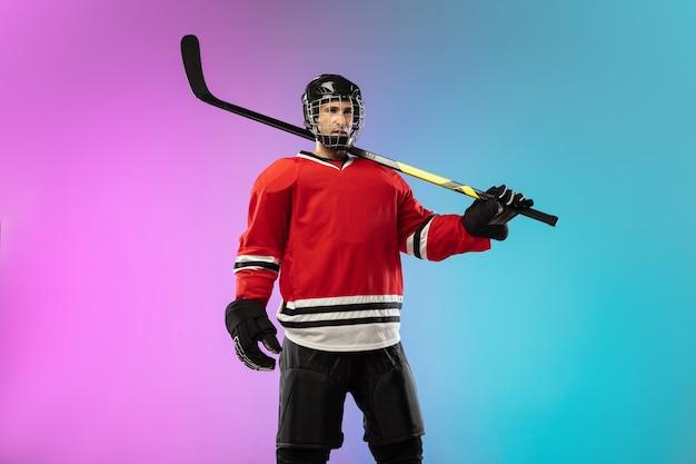 Männlicher hockeyspieler mit dem stock auf dem eisplatz