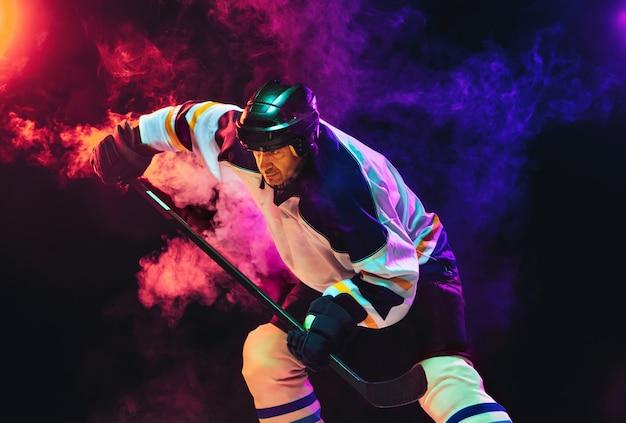 Männlicher hockeyspieler mit dem stock auf eisplatz und dunkler neonfarbener wand