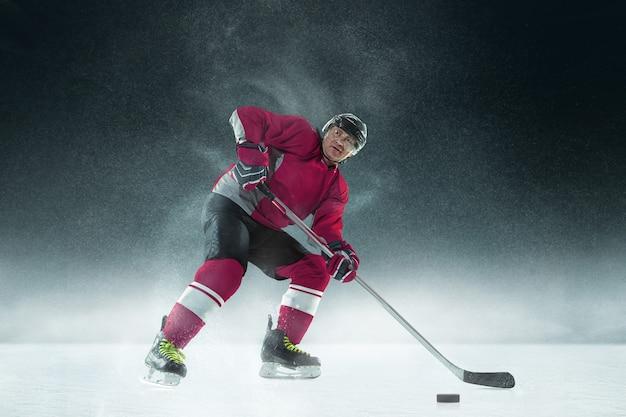 Männlicher hockeyspieler mit dem stock auf eisplatz und dunkler wand