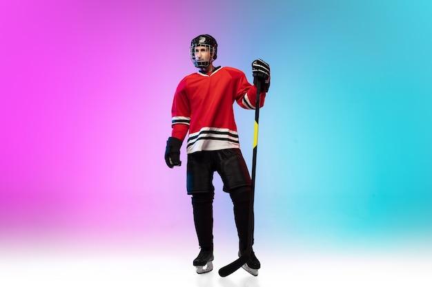 Männlicher hockeyspieler mit dem stock auf eisplatz und neongradientenraum