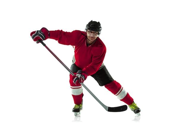 Männlicher hockeyspieler mit dem stock auf eisplatz und weißem hintergrund.