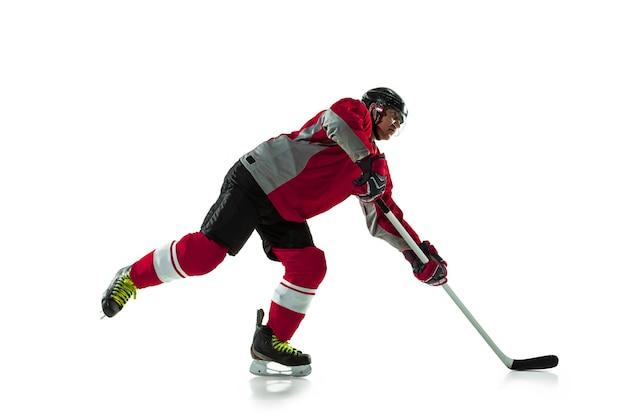 Männlicher hockeyspieler mit dem stock auf eisplatz und weißer wand