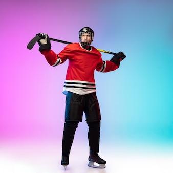 Männlicher hockeyspieler mit dem stock, der auf dem eisplatz und der neonfarbenen steigungswand posiert