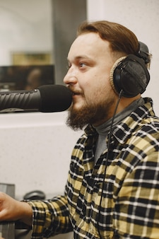 Männlicher host, der am mikrofon kommuniziert. mann im radiostudio.