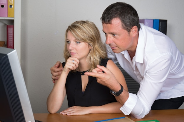 Männlicher hübscher manager mit ihrer sekretärin im büro
