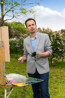 Männlicher hübscher verträumter künstler mittleren alters, der an einem bock- und staffelei-gemälde mit öl und acryl während eines kunstunterrichts in einem park arbeitet