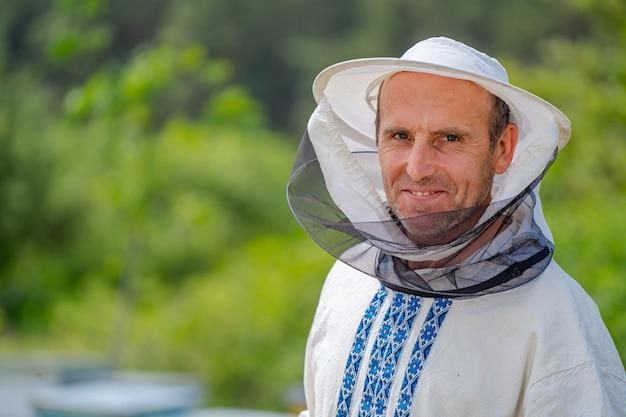Männlicher imker über bienenstockhintergrund. schutzhut. unscharfer hintergrund. honig und bienen.