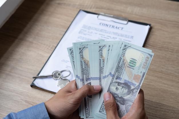 Männlicher immobilienmakler, der geld nach erfolgreichem abkommenvertrag für das kaufen des hauses zählt.