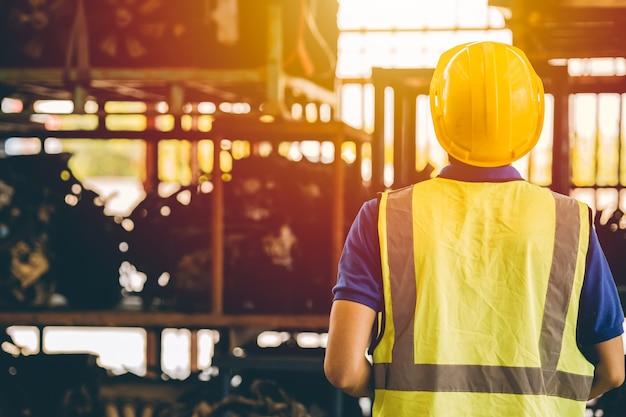 Männlicher ingenieur arbeiter rückansicht mit blick auf regal in der schwerindustrie fabrik metallarbeiten