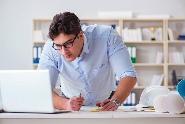 Männlicher ingenieur, der an zeichnungen und plänen arbeitet