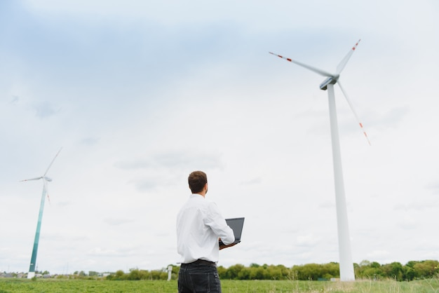 Männlicher ingenieur, der auf dem laptop im windturbinenpark arbeitet
