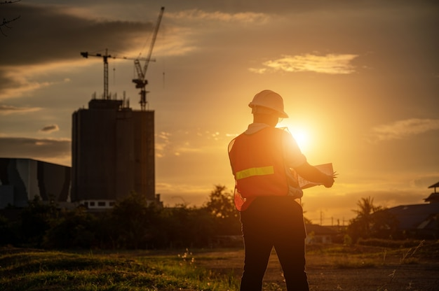 Männlicher ingenieur, der baustelle zur zeit des silhouette-sonnenuntergangs arbeitet