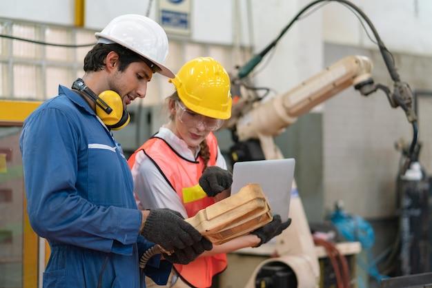 Männlicher ingenieur, der ferngesteuerte automatisierungsroboterarmmaschine verwendet, während weiblicher ingenieurprogrammierbefehl auf dem laptop in der fabrikindustrie