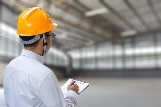 Männlicher ingenieur, der herein fabrik mit anmerkung über notizblock oder industrie eincheckt