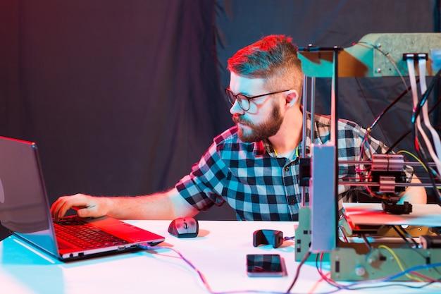 Männlicher ingenieur, der nachts im labor arbeitet, justiert er die komponenten eines druckers.