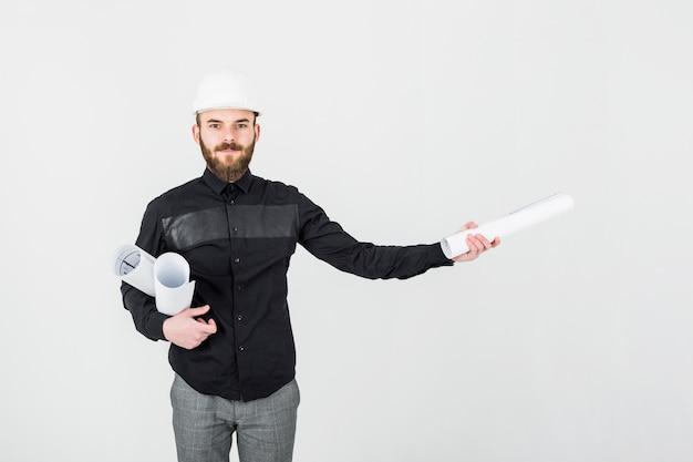 Männlicher ingenieur, der plan gegen weißen hintergrund hält