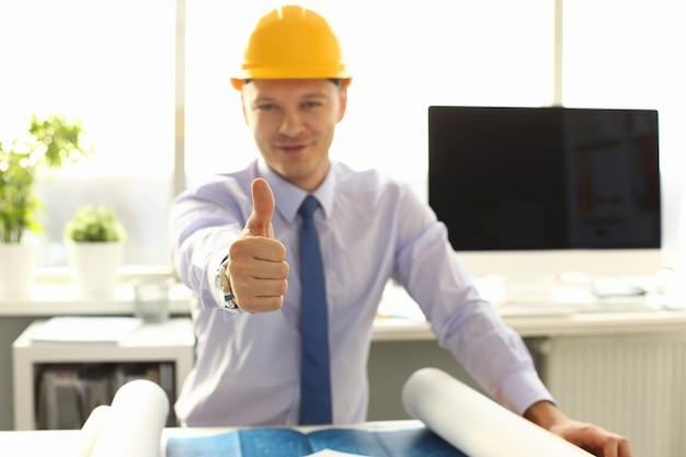 Männlicher ingenieur im gelben helm, der daumen oben zeigt