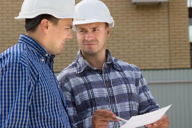 Männlicher ingenieur und vorarbeiter mittleren alters besprechen das hausprojekt auf der baustelle.