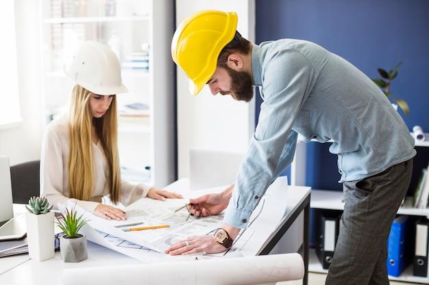 Männlicher ingenieurzeichnungsplan auf blauem druck mit architektenausrüstung