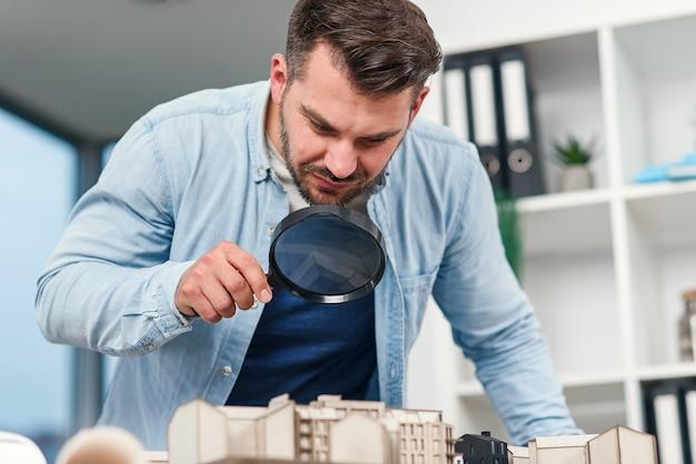 Männlicher inspektor des architekten untersucht ein hausmodell unter verwendung einer lupe hausinspektion und real