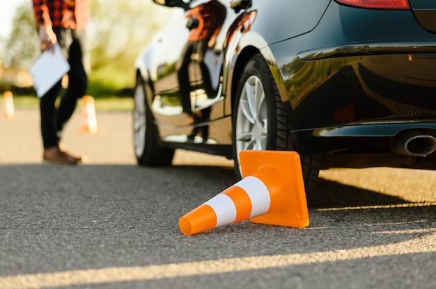 Männlicher instruktor am auto, umgestürzter verkehrskegel, unterricht in der fahrschule. mann, der dame beibringt, fahrzeug zu fahren. führerscheinausbildung