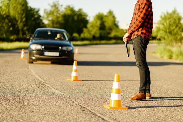 Männlicher instruktor, auto fährt zwischen den kegeln, unterricht in der fahrschule. mann, der dame beibringt, fahrzeug zu fahren. führerscheinausbildung