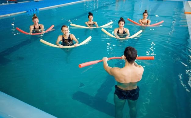 Männlicher instruktor und weibliche gruppe, aqua-aerobic-training im pool