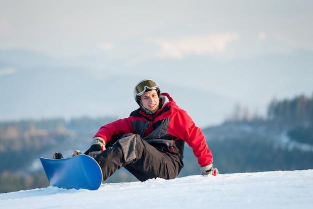Männlicher internatsschüler auf seinem snowboard am winer erholungsort