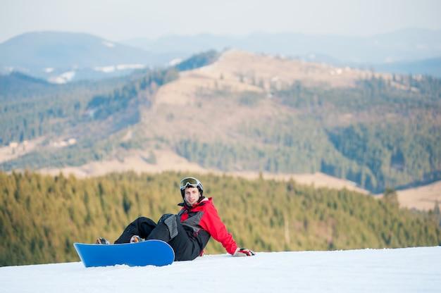 Männlicher internatsschüler auf seinem snowboard am winererholungsort