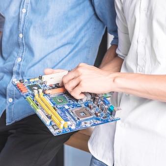 Männlicher it-techniker, der computermotherboard repariert