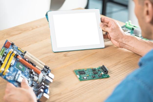 Männlicher it-techniker, der digitale tablette und motherboard hält