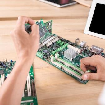 Männlicher it-techniker, der elektronisches computer mainboard auf holztisch repariert