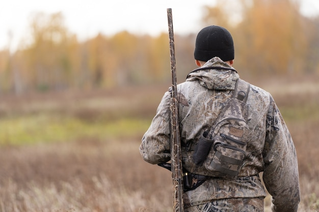 Männlicher jäger in tarnkleidung bereit, mit jagdgewehr zu jagen