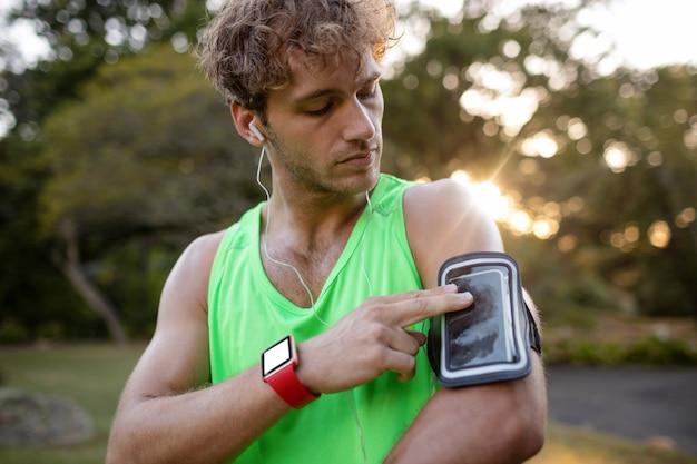 Männlicher jogger, der musik auf handy hört