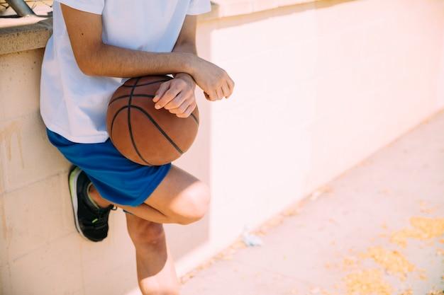 Männlicher jugendlich student, der am basketballplatz steht