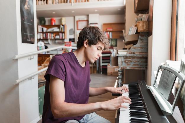 Männlicher jugendlicher, der klavier spielt