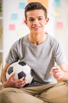 Männlicher jugendlicher, der zu hause sitzt und fußball hält.