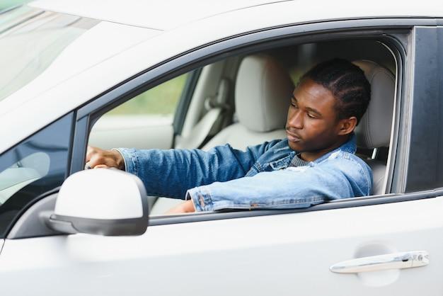 Männlicher jugendlicher fahrer, der aus autofenster schaut