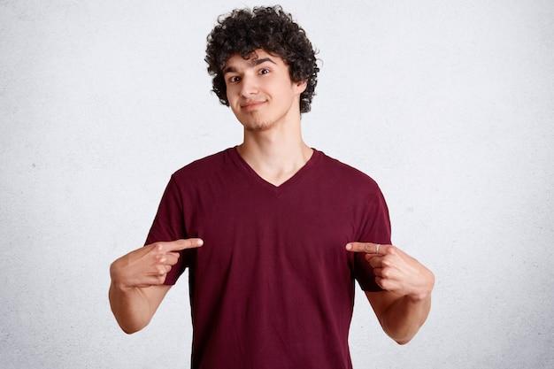 Männlicher junge mit knackigem dunklem haar, zeigt auf lässiges t-shirt, zeigt freien platz für ihr logo oder ihre werbung, isoliert auf weißer betonwand. menschen, kleidung, designkonzept