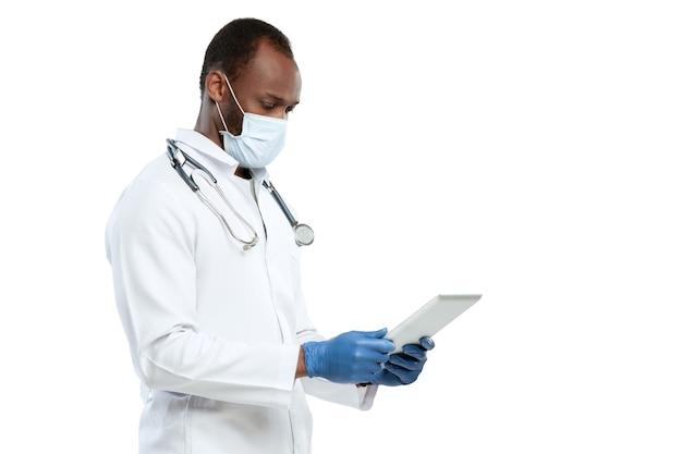 Männlicher junger arzt mit stethoskop und gesichtsmaske isoliert auf weißer wand