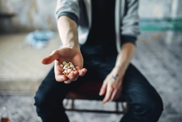 Männlicher junkie, der hand mit drogen ausstreckt