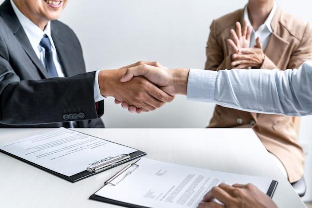 Männlicher kandidat händeschütteln mit interviewer oder arbeitgeber nach einem vorstellungsgespräch
