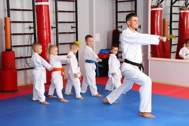 Männlicher karate-lehrer, der kleine kinder im dojo ausbildet