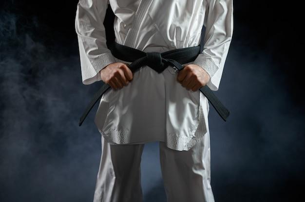 Männlicher karateka, kämpfer mit schwarzem gürtel, kampfhaltung. mann auf karate-training, kampfkunst, training vor dem kampf gegen wettkämpfe
