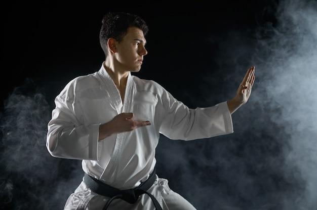 Männlicher karatekämpfer im weißen kimono, kampfhaltung. mann auf karate-training, kampfkunst, kampfwettbewerb