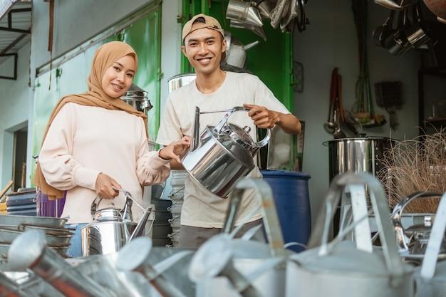 Männlicher kaufmann, der der asiatischen frau im haushaltsgerätegeschäft traditionelle kessel vorführt