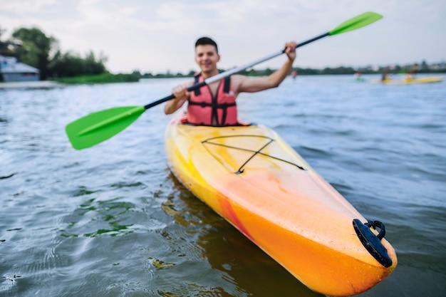 Männlicher kayaker, der kajak auf see schaufelt