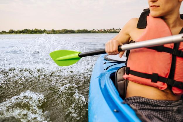 Männlicher kayaker, der wasser mit dem paddel beim kayak fahren spritzt