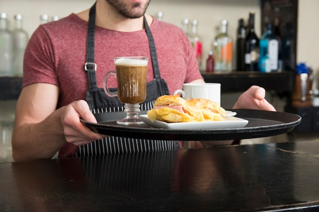Männlicher kellner, der hamburger und cocktail auf behälter in der bar hält